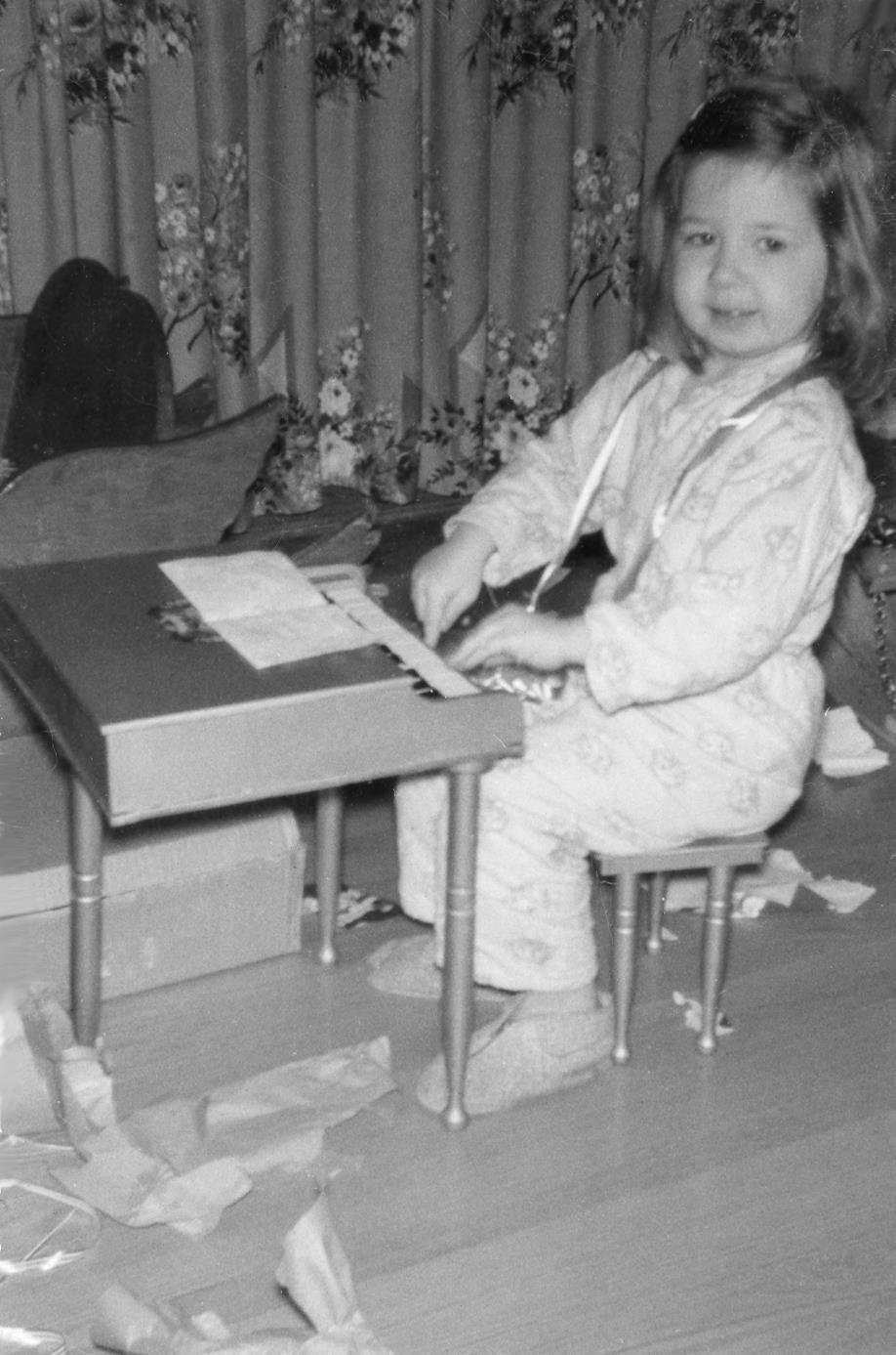 Probably about four, sitting at my toy piano at Christmas